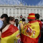 People drapped in a Spanish flags wait outside the Royal Palace in Madrid. Photo: Gerard Julien/AFP