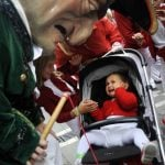 San Fermin is much more of a family event than outsiders initially imagine. Here a baby cries as a cabezudo (big-head) looks at her during a morning parade. Photo: Rafa Rivas/AFP