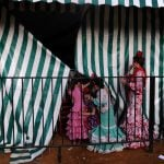 Young girls wear traditional Sevillana dresses in a <i>caseta</i> or small house. The fairgrounds are lined with these tents, which usually belong to prominent families or organizations in Seville.Photo: Cristina Quicler / AFP.