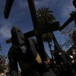 """A hooded members of the """"Los Estudiantes"""" brotherhood holds a cross during an Easter procession in Seville on March 31st.Photo: Cristina Quicler/AFP"""