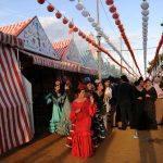 Women wearing traditional dresses walk the fairgrounds.Photo: Cristina Quicler / AFP.
