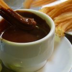 <b>Hot chocolate</b>: You can't visit Spain without sampling chocolate con churros or hot chocolate with churros, the long, donut-like snack popular across the country. Spanish hot chocolate is a far cry from the watery instant stuff so many of us are used to - it is a thick, luxurious treat that should not be missed. Photo: Omar Parada/Flickr