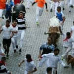 """Participants run in front of Jandilla bulls during the first """"encierro"""" (bull-run) of the San Fermin Festival in Pamplona, northern Spain, on July 7th.Photo: Cesar Manso/AFP"""