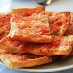 """<b>Pà amb tomàquet.</b> Meaning bread with tomatoes in Catalan, this is a typical dish in the region, simply made with toasted bread rubbed with tomatoes, olive oil and salt. It is often served with meats and cheeses.Photo: <a href=""""http://bit.ly/1CBJrRO"""">Javier Lastras</a> / Wikimedia Commons."""