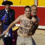 """A man is detained after jumping into the bullring with the sentence """"Fiesta without animal abuse"""" written on his body during the seventh corrida of the San Fermin Festival in Pamplona.Photo: Ander Gillenea/AFP"""