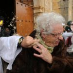 <b>El Gallo de Carnaval, Burgos.</b> Participants throw feathers and resin at a woman leaving church during the pagan celebration.Photo: Cesar Manso/AFP.