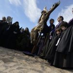 """Penitents from the """"Cristo Salvador"""" brotherhood stand around an effigy of Jesus Christ during a Holy Week procession on the beach in ValenciaPhoto: Jose Jordan/AFP"""