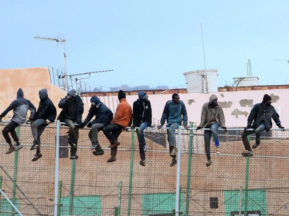 Migrants storm border fence from Morocco into Spain