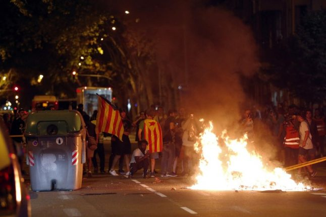 IN PICS: Catalan separatists' divisions erupt with late night clashes on referendum anniversary