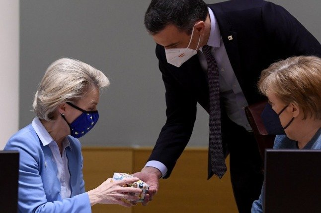 President of the European Commission Ursula von der Leyen (L) receives a gift from Spain's Prime Minister Pedro Sanchez as Germany's Chancellor Angela Merkel looks on during the second day of the EU summit at the European Council building in Brussels on May 25, 2021. - European Union leaders take part in a two day in-person meeting to discuss the coronavirus pandemic, climate and Russia. (Photo by JOHN THYS / POOL / AFP)