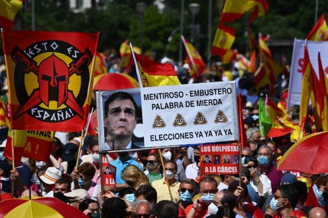 """People hold a banner displaying a picture of Spain's Prime Minister Pedro Sanchez reading """"Liar, elections now"""" during a protest by right-wing protesters to denounce controversial Spanish government plans to offer pardons to the jailed Catalan separatists"""