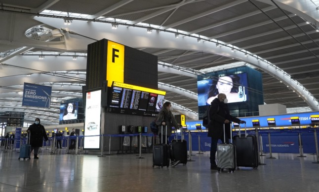 Travellers wearing face masks arrive at London's Heathrow Airport.