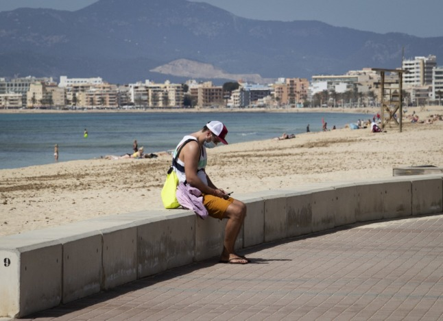 A tourists uses his mobile phone at a beach on the Balearic island of Mallorca in Spain.
