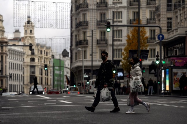 People walk with grocery bags under Christmas lights in the centre of Madrid.