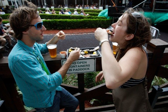 couple eats oysters and drinks beer