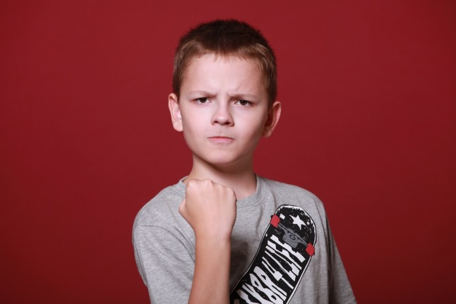 boy holds fist in anger, polite swearing in spanish