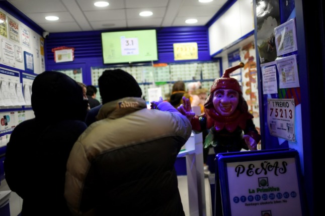 People queue to buy Christmas lottery tickets in Spain