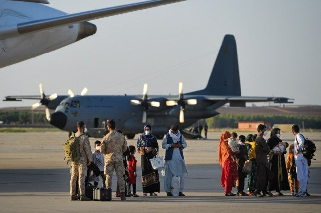 A group of Afghan nationals stand on the tarmac after disembarking from the last Spanish evacuation flight at the Torrejon de Ardoz air base near Madrid in August. Photo: PIERRE-PHILIPPE MARCOU / AFP)