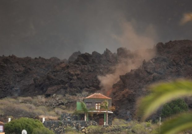 The lava flow from the Cumbre Vieja volcano smokes close to a house in the neighbourhood of Todoque in Los Llanos de Aridane on the Canary island of La Palma in September 24, 2021. - A fresh volcanic eruption in Spain's Canary Islands prompted the cancellation of flights, airport authorities said today, the first planes to be grounded after the Cumbre Vieja volcano came to life this week. New evacuations were also ordered as large explosions and new openings were reported at the volcano today. (Photo by DESIREE MARTIN / AFP)
