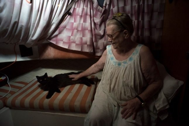 Margaretha Straates, 80, sits next to her cat on the boat where she and her husband are staying. Photo: Jorge Guerrero/AFP