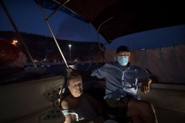 Margaretha Straates and Luis, 80 and 90 years old, wait on their boat where they have settled after fleeing their home following the eruption of the Cumbre Vieja volcano two weeks ago, in the port of Tazacorte, on the Canary Island of La Palma on October 3, 2021. - A new flow of highly liquid lava emerged from the volcano erupting in Spain's Canary islands on October 1, authorities said, as a huge magma shelf continues to build on the Atlantic ocean. (Photo by JORGE GUERRERO / AFP)