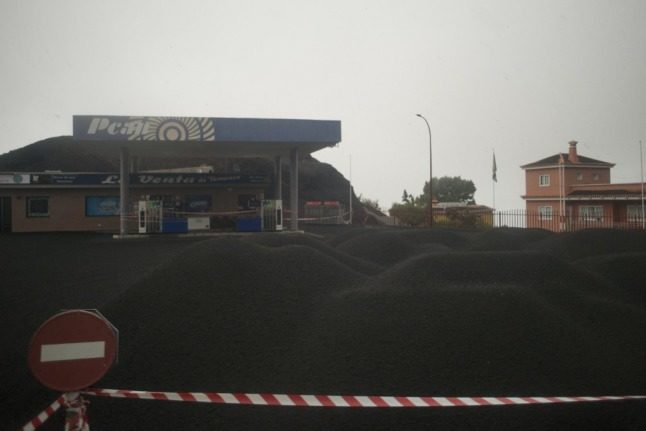 This photograph taken on October 4, 2021 shows a petrol station covered with ash, following the eruption of the Cumbre Vieja volcano, in Jedey, on the Canary Island of La Palma. - A new flow of highly liquid lava emerged from the volcano erupting in Spain's Canary islands on October 1, authorities said, as a huge magma shelf continues to build on the Atlantic ocean. (Photo by JORGE GUERRERO / AFP)
