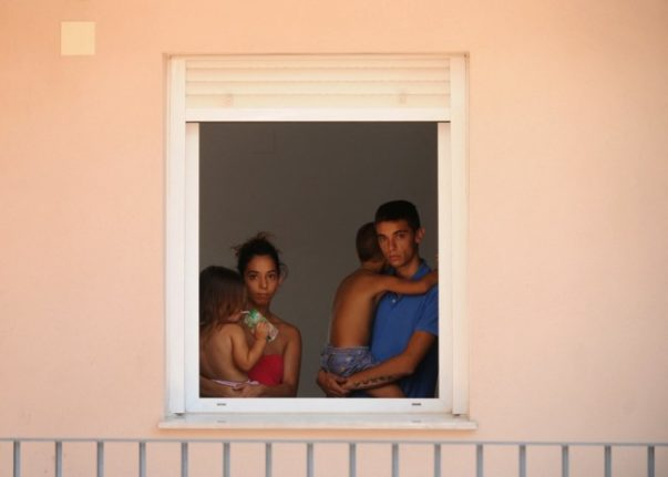 A young couple and their two infant children at the window in an occupied building in Sanlucar de Barrameda, near Cadiz. Photo: AFP PHOTO/ CRISTINA QUICLER